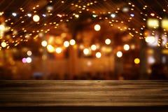 La imagen de la tabla de madera delante del extracto empañó el fondo de las luces del restaurante fotos de archivo