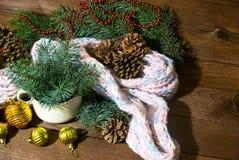 La imagen de la taza blanca con el Año Nuevo de la rama, de la bufanda y del oro del abeto juega en el fondo de madera Fotografía de archivo