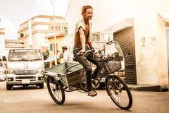 La imagen de trabajo del hombre chino de la entrega realiza movimiento del truco en su triciclo y lo impresiona paso-por fotos de archivo libres de regalías