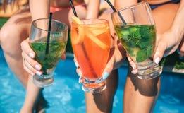 La imagen de tres mujeres coloridas de los cócteles se sostiene en manos Se sientan en el borde de la piscina y mantienen las pie fotos de archivo