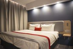 La imagen de un interior del dormitorio Una cama grande con cuatro almohadas Imágenes de archivo libres de regalías