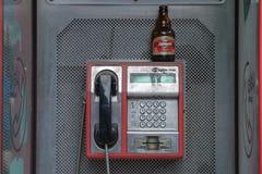 La imagen de una cabina de teléfono en la capital servia con una botella de cerveza se fue en el top de ella, después de una noch imagen de archivo