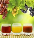La imagen de vidrios con el jugo en la uva agrupa el primer del fondo Fotografía de archivo