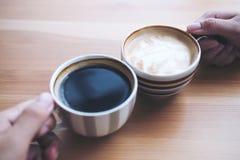 La imagen de la visión superior del ` s del hombre y de la mujer da sostener las tazas de café con la tabla de madera Imagen de archivo libre de regalías