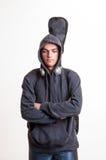 La imagen del adolescente en ropa negra y de la sudadera con capucha con los auriculares es Imágenes de archivo libres de regalías
