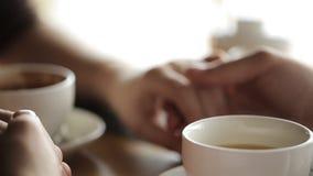 La imagen del amor del par querido que está llevando a cabo las manos y está teniendo una fecha en café con las bebidas calientes metrajes