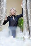 La imagen del blonde encantador dibuja las cortinas imagenes de archivo