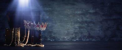 La imagen del cofre del tesoro de madera viejo abierto misterioso con la luz y la reina/el rey coronan con las piedras rojas de l imagenes de archivo