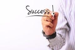 La imagen del concepto del negocio de una mano que detiene al marcador y escribe el éxito aislado en blanco Imágenes de archivo libres de regalías