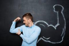 La imagen del hombre divertido con el músculo falso arma foto de archivo