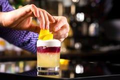 La imagen del primer del camarero da el adornamiento del cóctel con el limón Imágenes de archivo libres de regalías