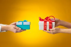 La imagen del primer de las manos del ` s del hombre y de la mujer con la caja de regalo Fotos de archivo libres de regalías