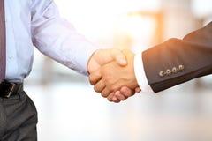 La imagen del primer de un apretón de manos firme entre dos colegas en el fondo blanco Imagen de archivo