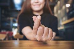 La imagen del primer de una mujer asiática con la cara sonriente hace una mini muestra de la mano del corazón Fotografía de archivo libre de regalías