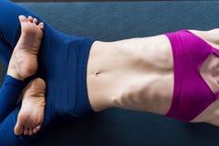 La imagen del primer del cuerpo femenino delgado en sujetador de los deportes y de las polainas que mentían en la estera que hací Imagen de archivo