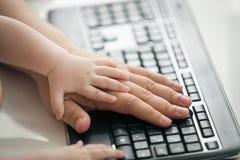 La imagen del primer del ` s del hombre y el ` s del bebé dan la mentira en el teclado de ordenador negro Concepto de tecnología  Fotos de archivo