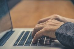 La imagen del ` s del hombre da mecanografiar en el teclado del ordenador portátil Foto de archivo
