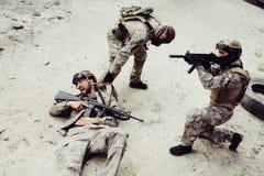 La imagen dramática del individuo consiguió herida Su camarada está intentando sacar de él el campo de batalla El tercer individu Foto de archivo libre de regalías