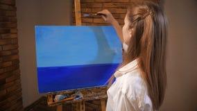 La imagen está en el caballete, la muchacha sube y comienza a dibujar Ella pinta paisaje, el cielo y el mar 4K MES lento almacen de metraje de vídeo