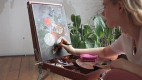 La imagen femenina joven de la vida de la calma de la pintura del artista con aceite pinta en el caballete en un estudio Arte, cr metrajes