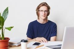 La imagen interior del oficinista de sexo masculino profesional talentoso con el peinado de moda, lleva gafas y la camiseta, se s foto de archivo