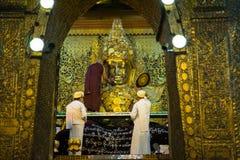 La imagen mayor de Mahamuni Buda del lavado del monje en el ritual del lavado de la cara de la imagen de Buda cada mañana en 4am Foto de archivo libre de regalías