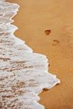 La imagen texturizada primer del pie imprime en una arena amarilla en un mar Imagen de archivo