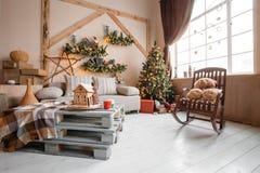 La imagen tranquila de la sala de estar casera moderna interior adornó el árbol de navidad y los regalos, sofá, tabla cubierta co Imagen de archivo