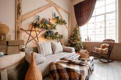La imagen tranquila de la sala de estar casera moderna interior adornó el árbol de navidad y los regalos, sofá, tabla cubierta co Fotos de archivo libres de regalías