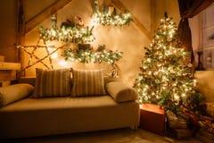 La imagen tranquila de la sala de estar casera moderna interior adornó el árbol de navidad y los regalos, sofá, tabla cubierta co Imagen de archivo libre de regalías