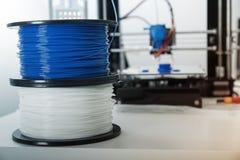 La impresora 3d y el ABS o el filamento personal del pla arrolla al lado de él imagen de archivo