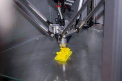 La impresora del metal 3D imprime la parte plástica amarilla Imagen de archivo