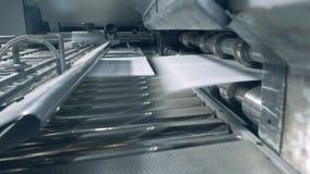 La impresora grande funciona con el Libro Blanco en un transportador en imprenta almacen de video