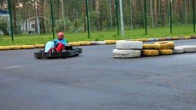 La impulsión del muchacho va kart en pista al aire libre almacen de metraje de vídeo