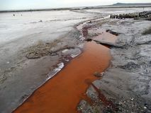 La impureza de sales coloreó el agua de una corriente en naranja imagen de archivo