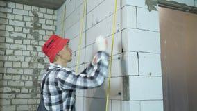 La inclinación para arriba tiró del constructor que instalaba las abrazaderas en la pared aireada del bloque de cemento almacen de metraje de vídeo