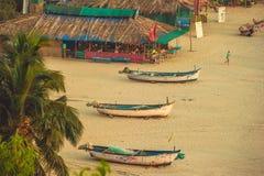 La India, Goa - 9 de febrero de 2017: Tres barcos blancos en una playa arenosa foto de archivo