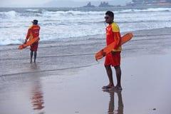 La India, GOA, el 28 de enero de 2018 Los salvadores de los hombres caminan a lo largo de la orilla en ropa roja, silbido en el s fotos de archivo