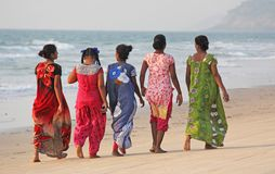 La India, GOA, el 22 de enero de 2018 Un grupo de mujeres indias en saris brillantes y coloridas va a lo largo de la costa o de l fotografía de archivo libre de regalías