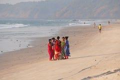 La India, GOA, el 22 de enero de 2018 Un grupo de mujeres indias en saris brillantes y coloridas va a lo largo de la costa o de l imagen de archivo libre de regalías