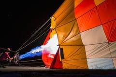 La inflación de un globo muy colorido con la llama se encendió en la noche Fotografía de archivo libre de regalías