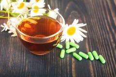 La infusión de hierbas en una taza transparente, cápsulas y manzanilla florece en la tabla de madera El concepto de phytotherapy Imagen de archivo libre de regalías