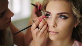 La ingravidez se pinta con un cepillo de pestañas Maquillaje profesional para la mujer con la piel joven sana de la cara almacen de video