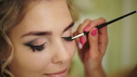 La ingravidez se pinta con un cepillo de pestañas Maquillaje profesional para la mujer con la piel joven sana de la cara almacen de metraje de vídeo