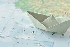 La inmigración y pide el concepto del asilo - barco de papel en mapa fotos de archivo