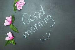 La inscripción 'buena mañana 'en tiza cerca de las flores libre illustration