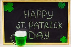 La inscripción con tiza verde en una pizarra: El día de St Patrick feliz Hojas del trébol blanco Una taza con la cerveza verde Imagenes de archivo