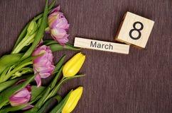 La inscripción el 8 de marzo con las flores en un fondo gris Fotografía de archivo libre de regalías