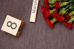 La inscripción el 8 de marzo con las flores en un fondo gris Imágenes de archivo libres de regalías