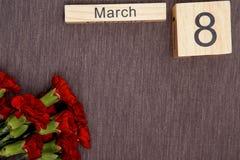 La inscripción el 8 de marzo con las flores en un fondo gris Fotos de archivo